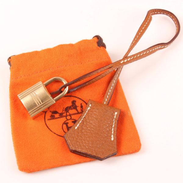 Imagen de la clochette y el candado del bolso hermes birkin 35 togo gold