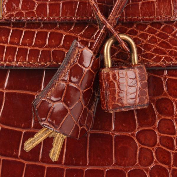 Imagen de la clochette y candado del bolso Hermès Kelly 32 de cocodrilo en color whisky.