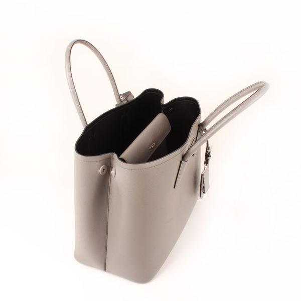 Imagen del interior abierto del bolso prada saffiano gris
