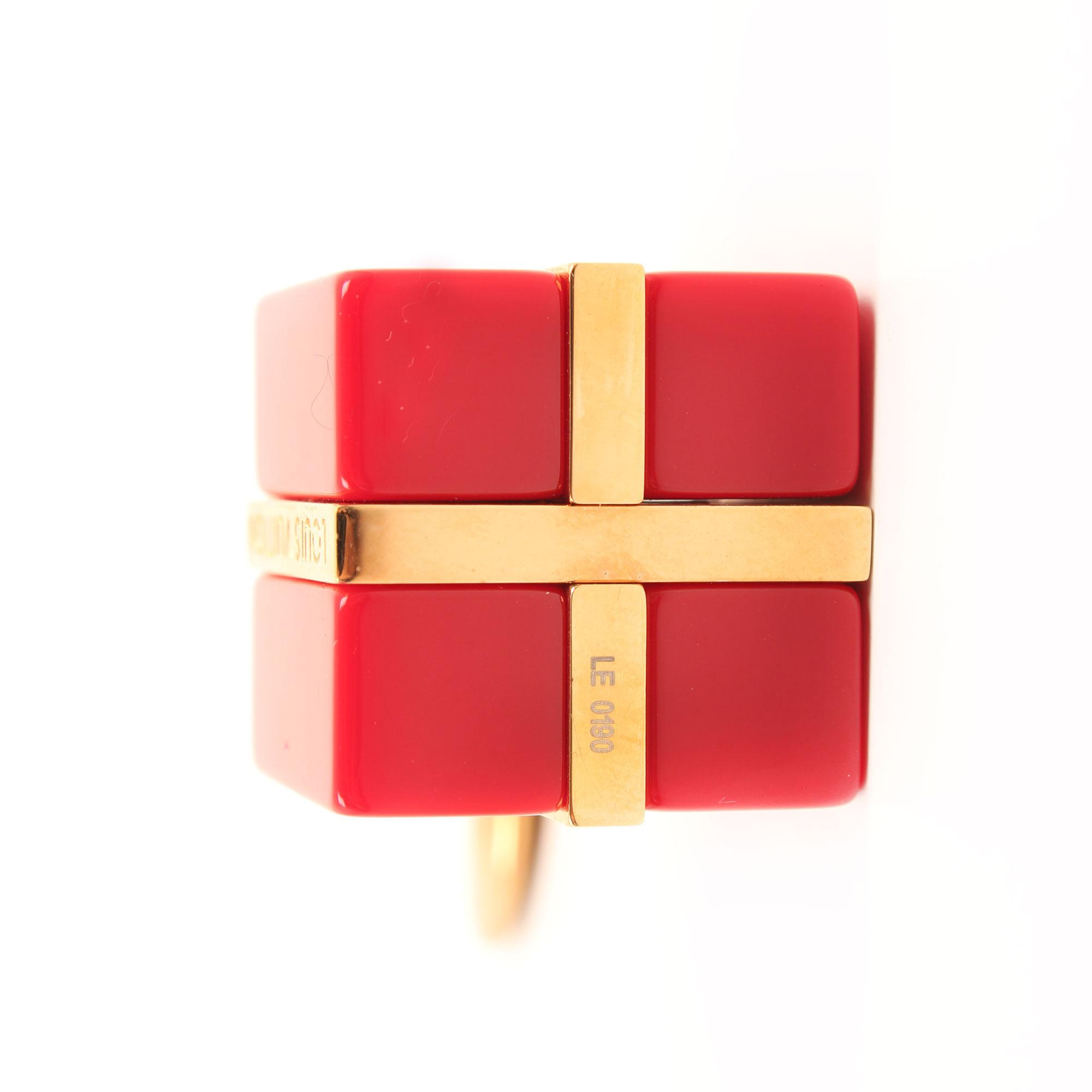 Imagen de la base del charm bolso louis vuitton dorado y rojo