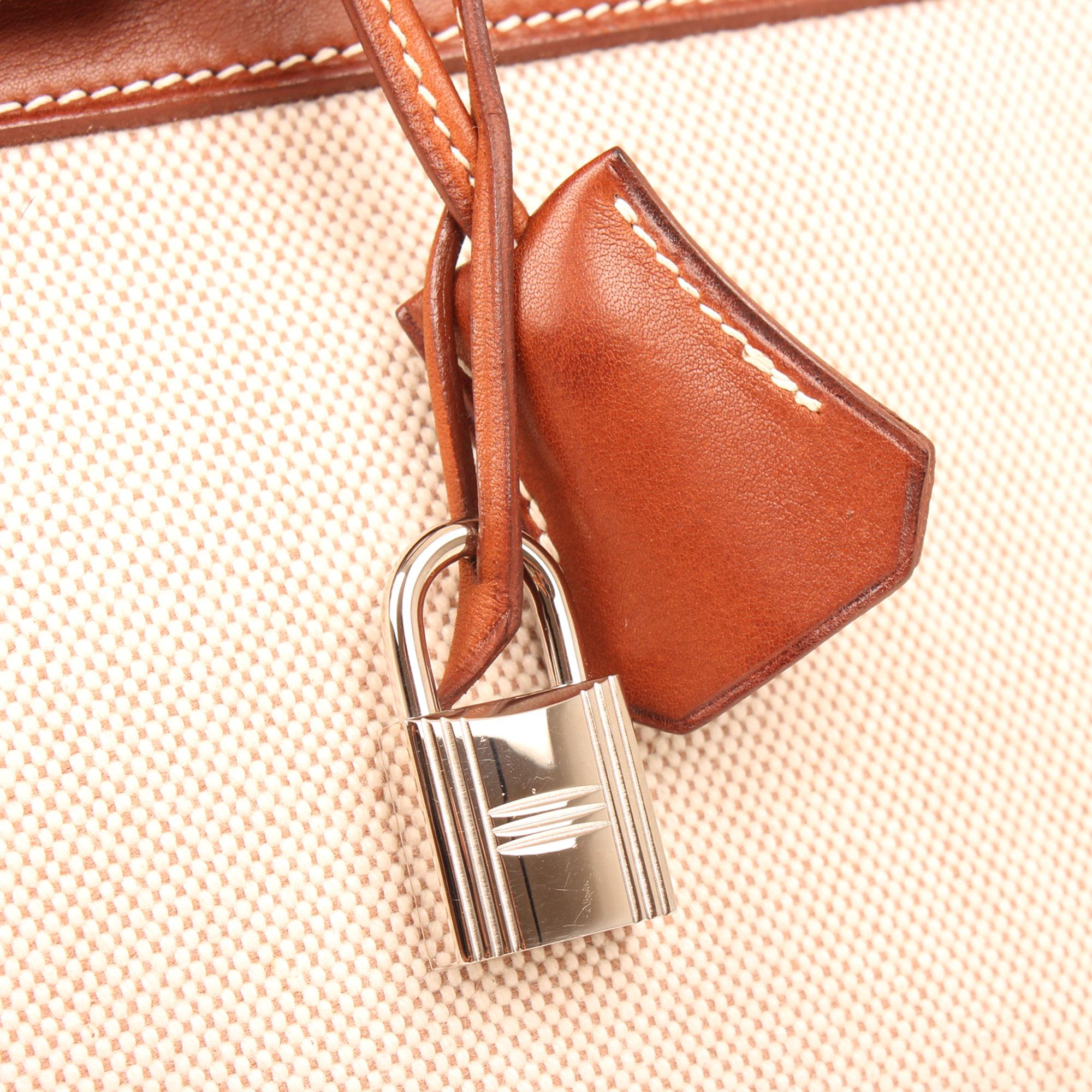 Imagen de detalle del candado y llaves del bolso hermes birkin 35 barenia lona